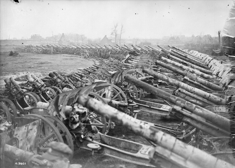 Canadian War Records office Official photograph O-3601, in the same series as the above, shows the crescent of guns from the other direction. Interesting pieces include an Austrian infantry gun, several old 105mm short howitzers without recoil systems (sFH98), and at least one gun with a blown muzzle.