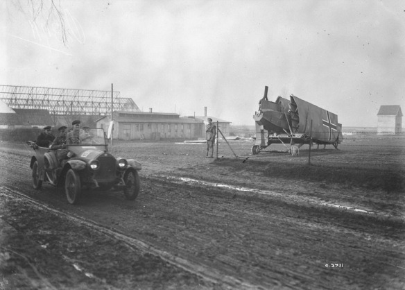 "Nov. 1918. There is a lot of interest in this photo.  The soldier guarding the plane, the enorous Zeppelin shed, and the officer""s car in the foreground."